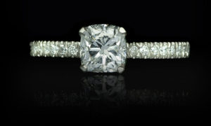 Platinum engagement ring, cushion cut centre stone weighing 1.00 carat. Micro-set diamond shoulders
